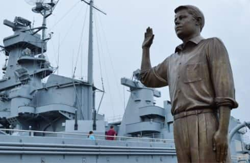 Bronze statue of a man next to large naval ship