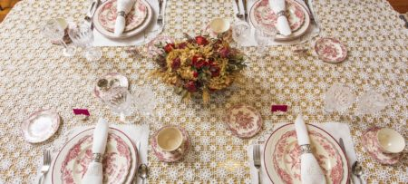 Dining table with delicate knitted tablecloth, Victorian red and white China plates, folded napkins, and red and yellow flower arrangement