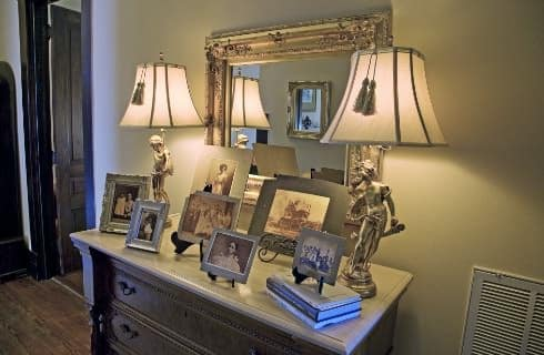 Victorian dresser with antique pictures and frames on top and two lamps with antique mirror hanging above