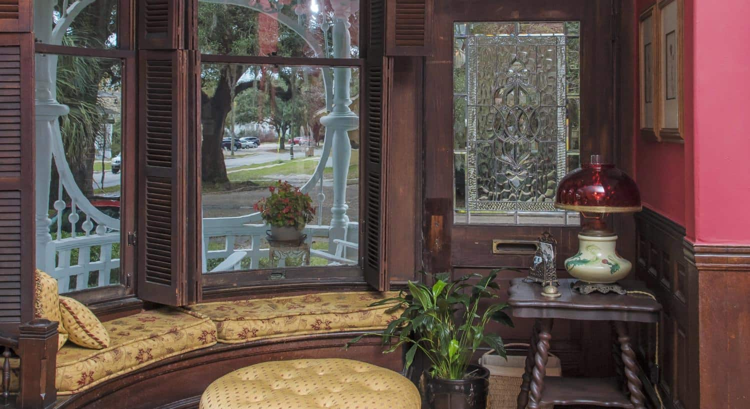 Large picture window with dark brown wooden shutters and gold and burgundy floral upholstered cushions