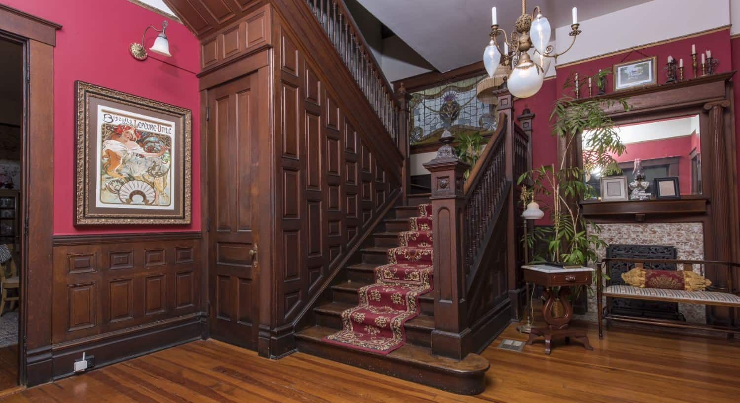 Large staircase with dark brown ornate wood railing and paneling with floral burgundy stair runner