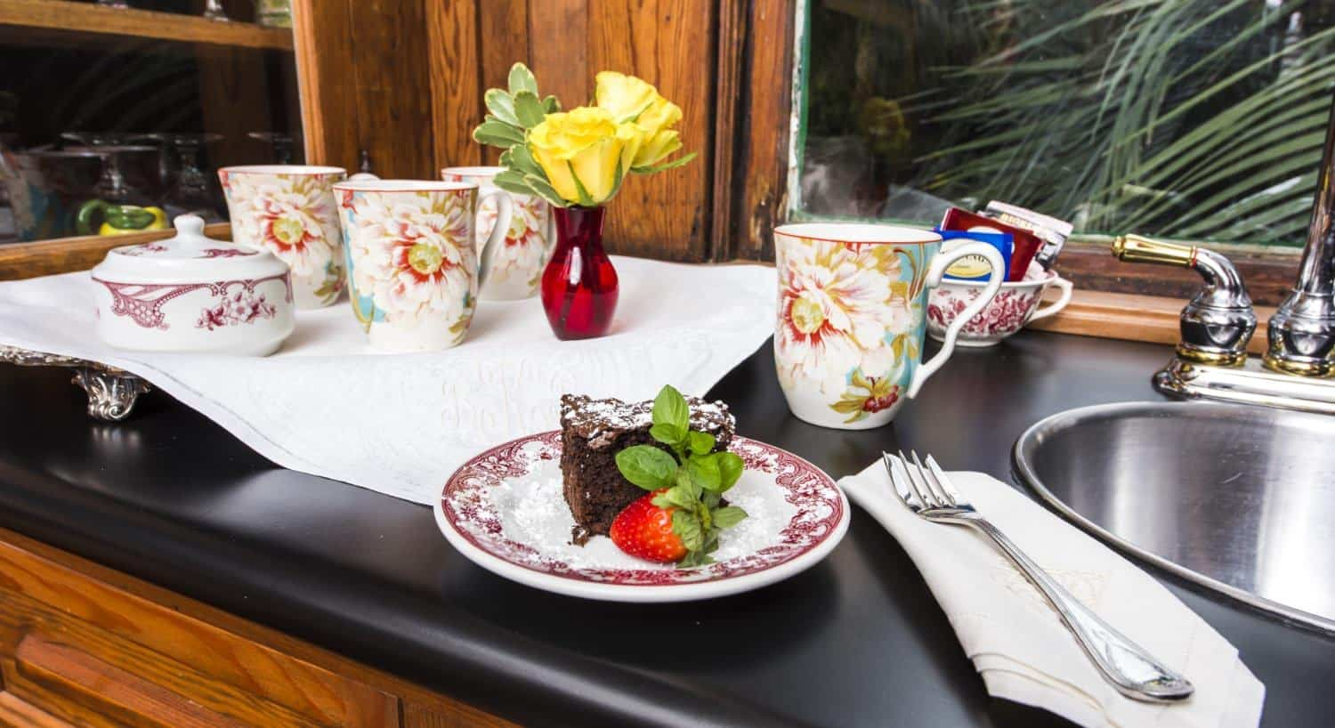 Red and white China plates with chocolate cake dusted with powdered sugar, strawberry, and mint leaves
