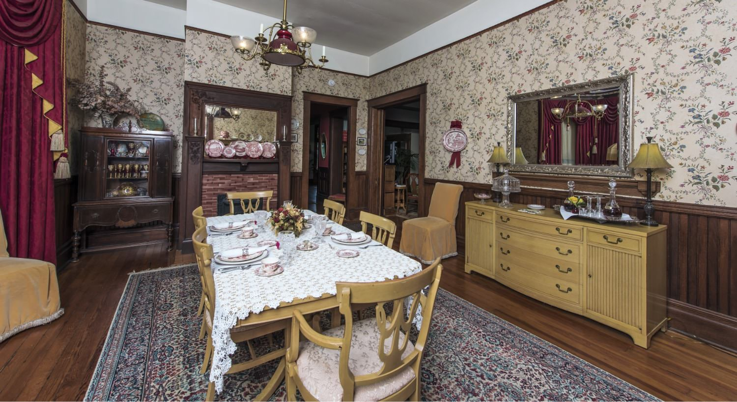 Dining room with light brown table, chairs, and buffet, dark brown hardwood floors, and floral wallpaper