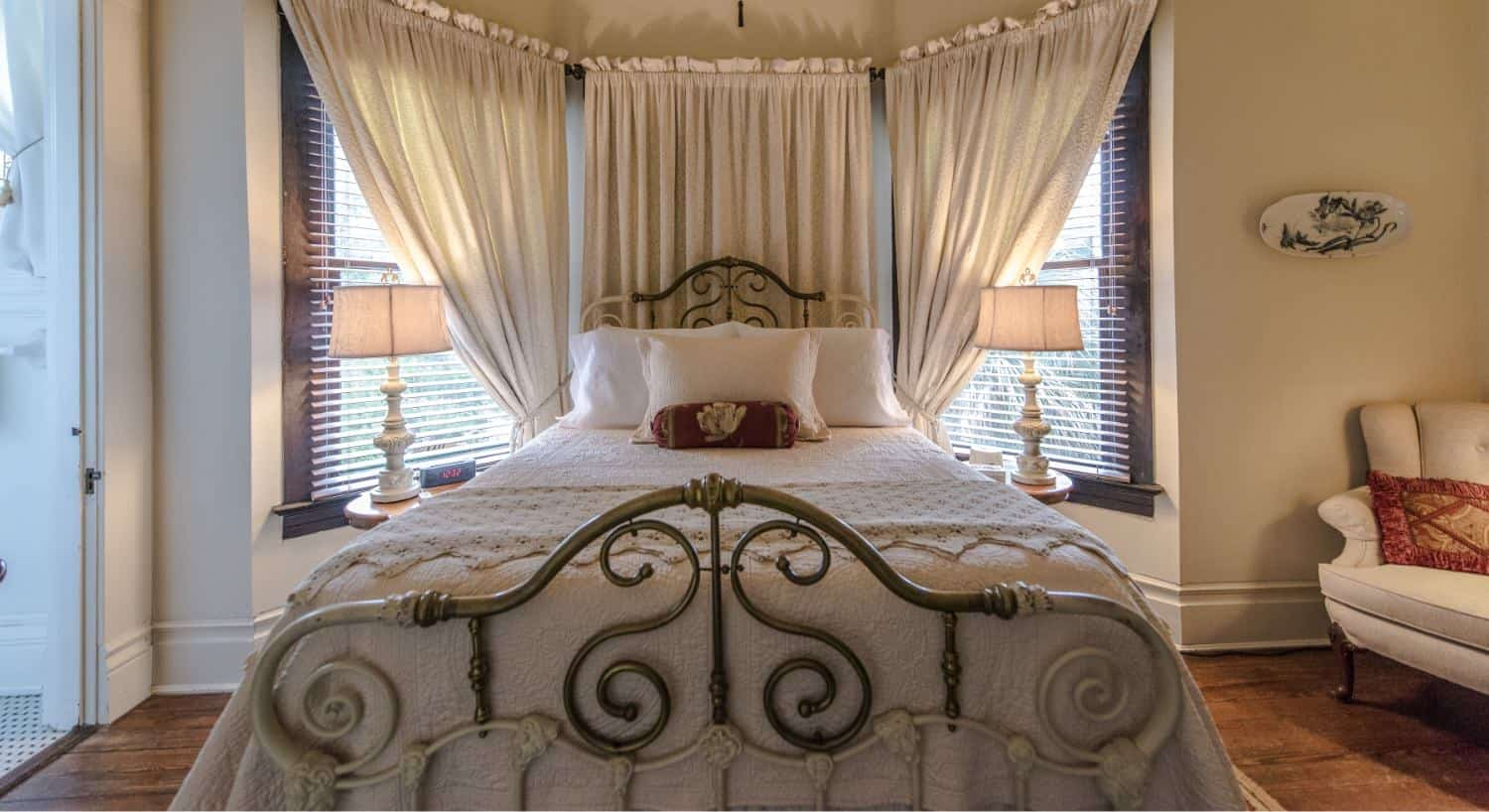 Bedroom with cream-colored walls, hardwood floors, iron bed with cream bedding, and cream upholstered chair