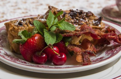 Red and white China plates with pecan topped french toast, thick-cut bacon, strawberry, and cherries