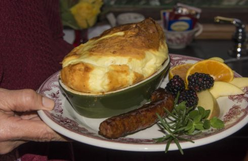 Red and white China plate with egg souffle dish, link sausage, blackberries, and apple and orange slices