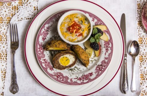 Red and white China plate with hardboiled egg dish, side of grits, blackberries, and apple slices