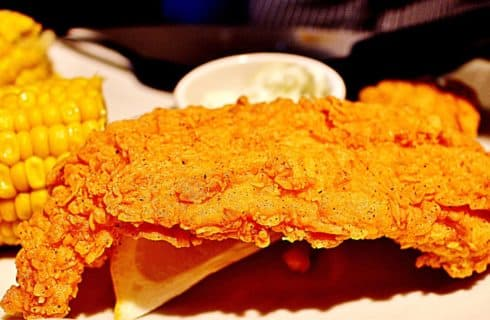 Close up view of fried chicken and corn on the cob
