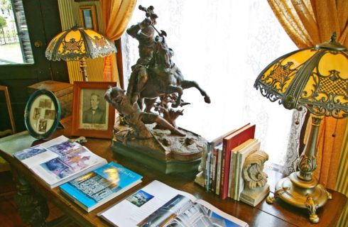 Old wooden table with books, old pictures and frames, antique lamps, and bronze miniture statue on top