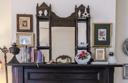 Dark wooden mantel with Victorian mirror, old kerosene lamps, and books