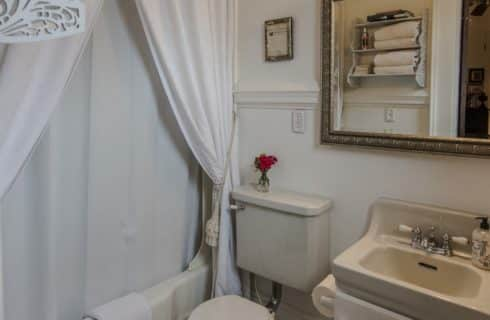 Bathroom with white walls, cream toilet, cream sink, cream bathtub, and white curtains