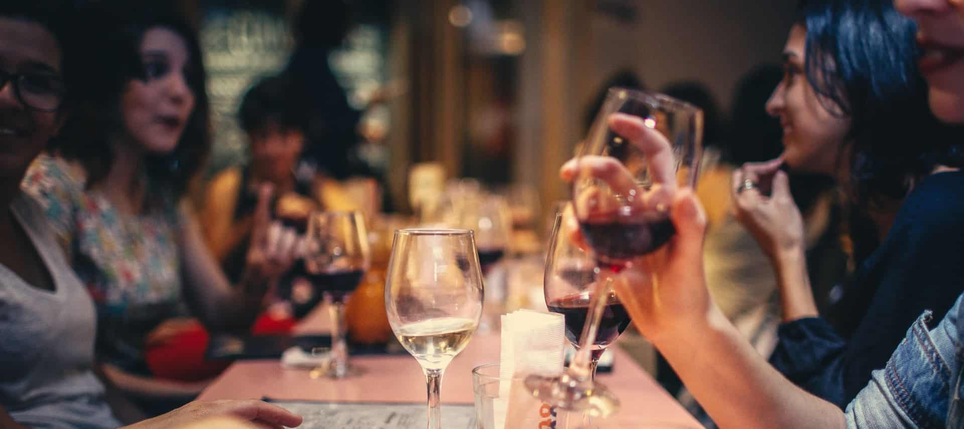 People at a restaurant sitting at a table talking, laughing, and drinking wine