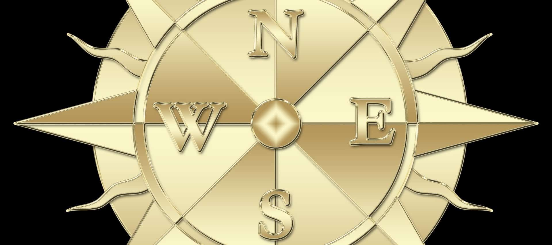 Gold compass with N, E, S, W on a black background