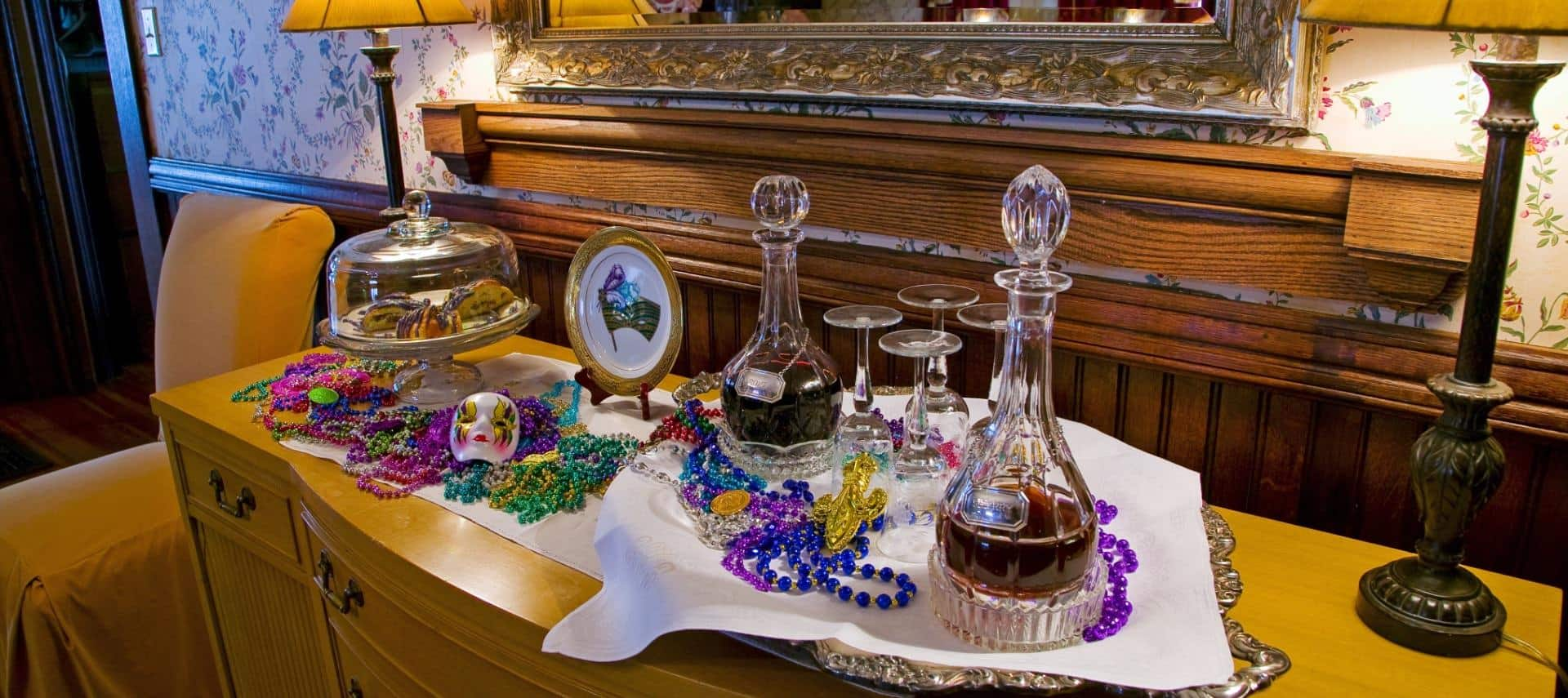 Large wooden buffet topped with Mardi Gras decorations, pastries in glass container, alcohol in glass decanters, and wine glasses