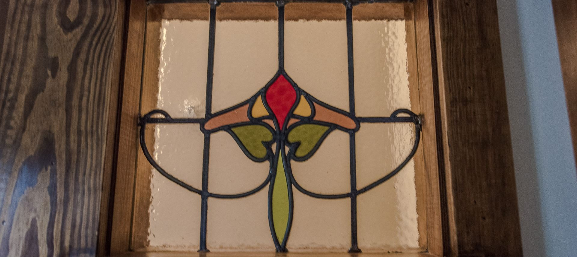 Wooden door with stained glass insert of a red, yellow, and pink flower with green stem